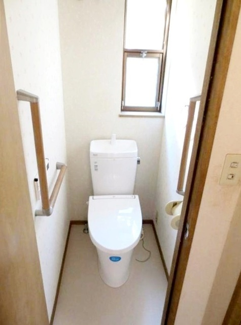 1階 温水洗浄便座仕様。 バリアフリーに配慮して便座から立ち上がりやすくする手すりを設置。また棚やタオル掛けも設けています。