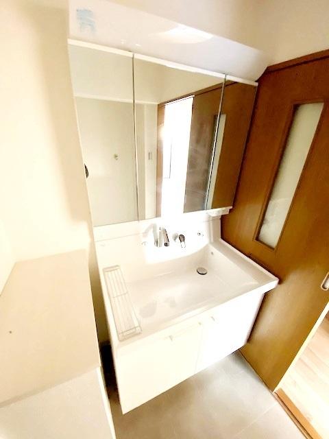 シャワー機能付き洗面化粧台新規交換。 三面鏡の裏には収納がございます。 家族の歯ブラシや、奥様の化粧水等をスッキリ整理整頓できます。
