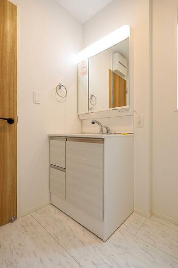 大きな鏡と明るいライトが特徴的な洗面台。